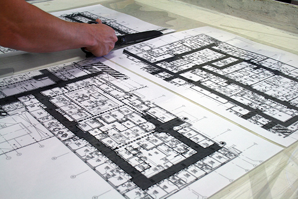 A pair of hands trims a set of architectural drawings