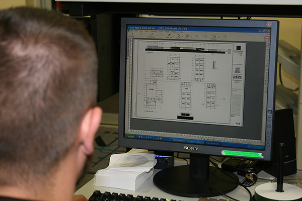 Looking over a pressworker's shoulder as they access secure files on the computer