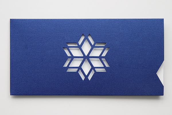 A blue envelope with a white card visible through a die-cut snowflake