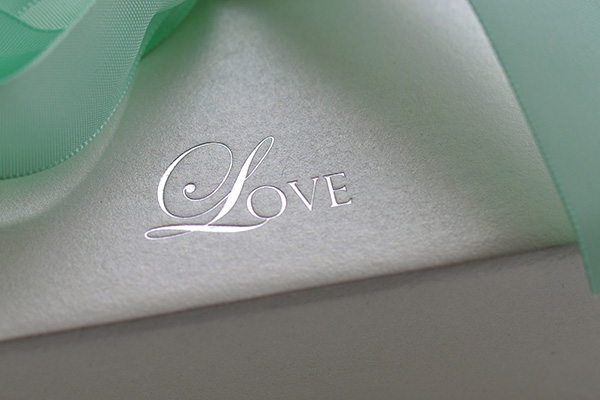 The word love printed in silver foil against a textured white paper with a mint green ribbon framing the card