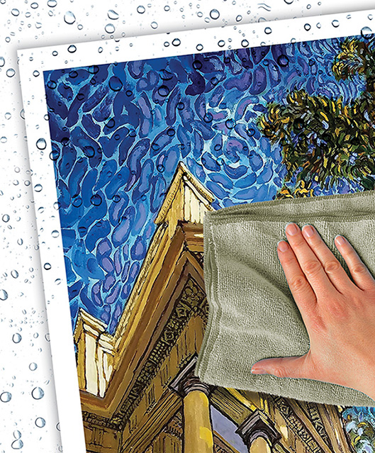 A poster print of a painted Charlottesville building covered in water droplets while a hand wipes them away with a cloth